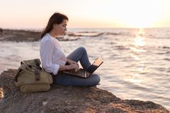 Be free, work whenever you want. Freelancer girl working on the beach stock photo