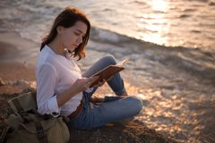 Be free, work whenever you want. Teenage girl reading book on the beach in sunset royalty free stock images