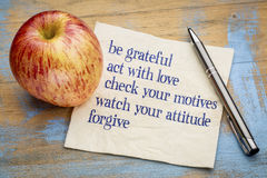 Be grateful - inspirational phrases on napkin. Be grateful, act with love and other inspirational phrases - handwriting on a napkin with a fresh apple stock photography