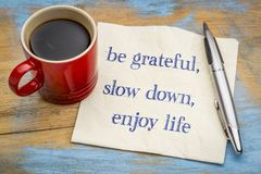 Be grateful, slow down, enjoy life. Inspirational handwriting on a napkin with a cup of coffee stock images