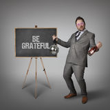 Be grateful text on blackboard with businessman Stock Photography