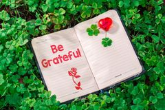 Be grateful text in notebook. On Clovers with red heart in the garden stock photography