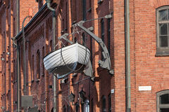 A be hanging boat on old red brick wall Stock Photography
