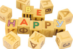 Be happy. Wooden bricks with letters, 'be happy' in English, surrounded by Russian characters, isolated Stock Photography