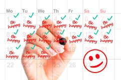Be happy every day of your life concept with woman handwriting reminders. On calendar Royalty Free Stock Photography