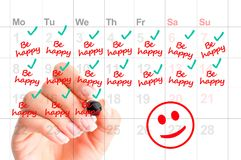 Be happy every day of your life concept with woman handwriting reminders. On calendar Stock Photo