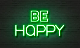 Be happy neon sign on brick wall background. Royalty Free Stock Photo