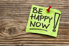 Be happy now reminder note. Against grained weathered wood stock photography