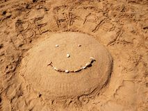 Be Happy!. Sand and sea shells  and pebbles 'Be Happy' with the 'Smile' sign, at the beach on a sunny day Stock Images