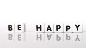 Be Happy. Spelled in black letters reflected on white background Royalty Free Stock Images