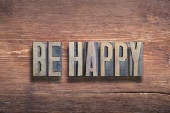 Be happy wood. Be happy phrase combined on vintage varnished wooden surface stock images