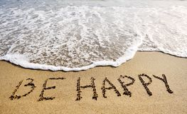 Be happy words written on beach sand-positive thinking concept. Be happy words written on the sand of the beach - positive thinking concept Royalty Free Stock Photos