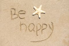 Be happy written on white sand, beach background Royalty Free Stock Images