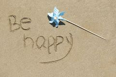 Be happy written on white sand, beach background Stock Photography