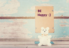 Be happy wrote paper stand and cute bear on grunge blue wooden b. Ackground Stock Photo
