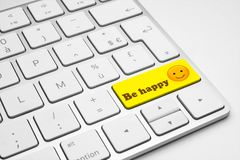 Be happy yellow button with an emoticon on a white isolated keyboard. Be happy yellow button with a happy face emoticon on a white isolated keyboard. Happiness Stock Photo