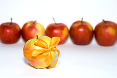 Be individual!. Red apples behind a yellow apple with a gift bow Stock Image