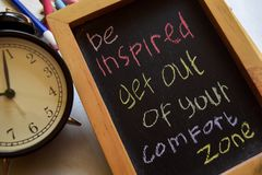 Be inspired get out of your comfort zone. On phrase colorful handwritten on chalkboard, alarm clock with motivation and education concepts stock photography