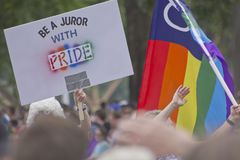 Be a Juror With Pride slogan on board and rainbow flag  at Portland Oregon pride parade. Two people holding signs at the Portland Oregon gay pride parade Royalty Free Stock Photo