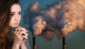 Be kvinnan mot av rör som förorenar en atmosfär Royaltyfri Foto