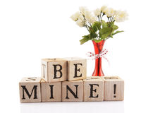 Be Mine!. Alphabet blocks arranged to spell Be Mine!  A red vase filled with white roses is nearby.  Isolated on white Stock Images