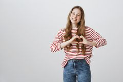 Be mine forever. Portrait of passionate attractive blonde girl showing heart gesture over chest and smiling broadly. Confessing in love and showing true stock photos