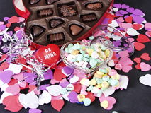 Be Mine Hearts. Multi colored heart cut outs spilled around a glass heart shaped box full of conversation heart candies, and a heart shaped box of chocolate stock photography