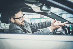 Be more careful in driving. Enraged male driver shouts and gestures threateningly royalty free stock photography