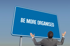 Be more organised against blue sky. The word be more organised and businessman posing with arms raised against blue sky Stock Images