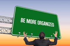 Be more organized against purple and orange sky. The word be more organized and gesturing businessman against purple and orange sky Royalty Free Stock Photography