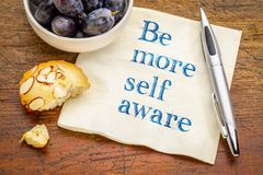 Be more self aware - advice on napkin. Be more self aware reminder - handwriting on a napkin with grapes and cookie royalty free stock photo