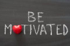 Be motivated. Phrase handwritten on school blackboard royalty free stock image