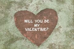Be My Valentine. A concrete slab with a red heart shape in the middle that says, Will You Be My Valentine Royalty Free Stock Photography