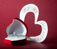 Be my valentine. Red box with diamond ring and card with text on red background Royalty Free Stock Photos