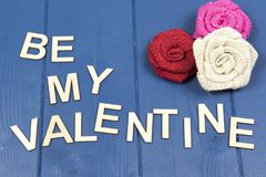 Be my valentine on a blue background. With colourful fabric roses Stock Photos