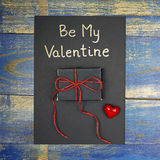 Be My Valentine card with gift box and red heart. On wooden background Royalty Free Stock Photography