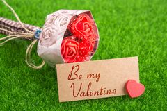 Be my valentine. In card with heart and bouquet on grass Stock Photography