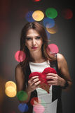 Be my Valentine. Conceptual image of a beautiful sexy romantic young woman holding a red heart surrounded by circular bokeh representing colourful party lights Stock Photos
