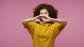 Be my Valentine! Cute happy girl afro hairstyle in hoodie making heart shape with hands and kissing air