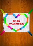 Be My Valentine inscription red color greeting card sheet of notepad paper in heart shape on the wooden background. Be My Valentine inscription red color Royalty Free Stock Photography