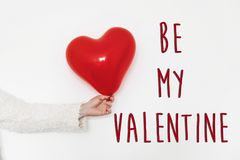 Be my valentine text sign. happy valentine`s day concept. hand h. Olding  red heart balloon on white background with space for text. greeting card Stock Photography