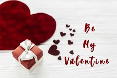 Be my valentine text sign. stylish present box and velvet hearts. On white wooden background. happy valentines day concept. greeting card with space for text Stock Photos