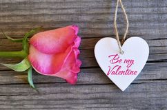 Be my Valentine.Valentines Day greeting card.Rose and decorative white heart on old wooden background.St.Valentine`s Day concept. royalty free stock image