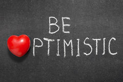 Be optimistic. Phrase handwritten on blackboard with heart symbol instead of O Royalty Free Stock Photos