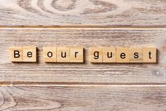 Be our guest word written on wood block. Be our guest text on table, concept.  Royalty Free Stock Images