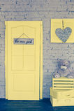 Be our guest. Wording on wooden board hanging on yellow door with gray accessories. Welcome concept. Toned image Stock Photos