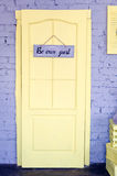 Be our guest. Wording on wooden board hanging on yellow door. Welcome concept. Toned image Stock Photo