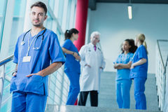 Be part of the integrated team of doctors. Satisfied intern stands in front of the stairs when his colleagues speak with a supervisor Stock Photography