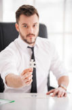 Be a part of our team!. Confident young man in shirt and tie showing the last element from puzzle while sitting at his working place Stock Images
