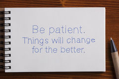 Be patient handwritten text on a notebook with pen. Recycled paper notebook with tex be patient on wooden background Stock Photography
